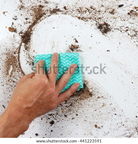 Hand with rag cleans the heavily dirty surface - stock photo