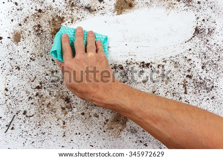 Hand with rag wiping a dirty surface - stock photo