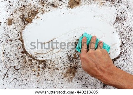Hand with rag wiping a very dirty surface - stock photo