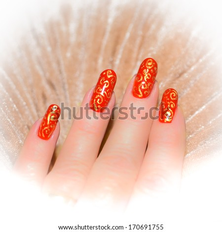 hand with red nails with gold pattern on a beige background