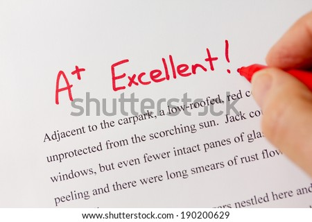 Hand with Red Pen Grading Successful Essay with Excellent - Success concept in education industry   - stock photo