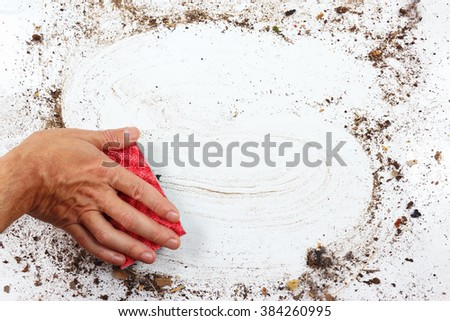 Hand with red sponge cleans a heavily dirty surface - stock photo