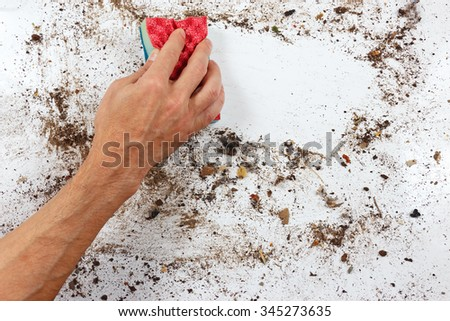 Hand with red sponge cleans a very dirty surface - stock photo