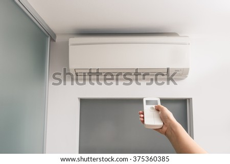 Hand With Remote Control Directed On The Air Conditioner in the room - stock photo