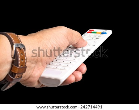 Hand with remote control isolated on black background - stock photo