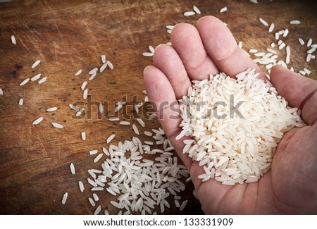 Hand with rice and wooden table. - stock photo