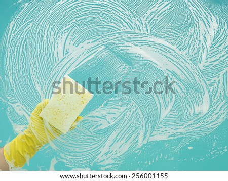 hand with rubber glove cleaning window with sponge and detergent
