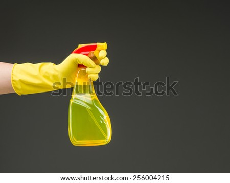 hand with rubber glove holding cleaning spray bottle against grey background - stock photo