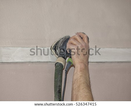 Hand with sanding machine on wall