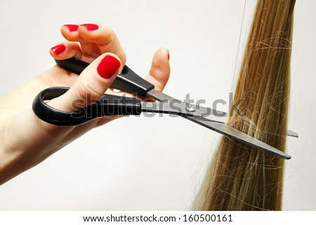 hand with scissors cutting long hair - stock photo