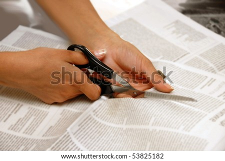 hand with scissors cutting out an article from newspaper - stock photo