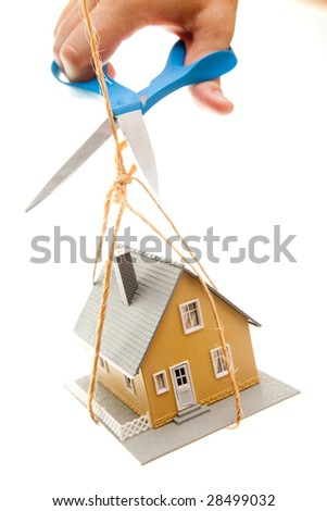 Hand with Scissors Cutting String Holding House Isolated on a White Background. - stock photo