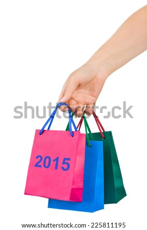 Hand with shopping bags 2015 isolated on white background - stock photo