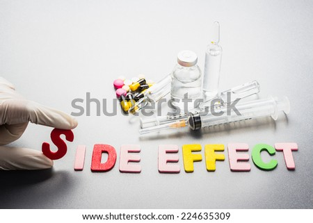 Hand with Side Effect word and medical equipment - stock photo