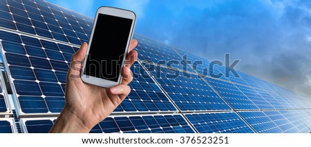 Hand with smart phone and solar panels
