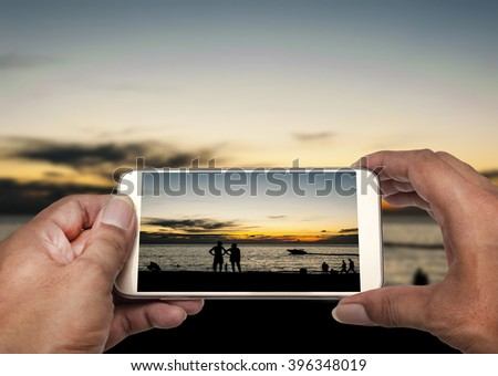 Hand with smart phone shooting photograph on blurred silhouette some people relax and beach sunset in twilight  - stock photo