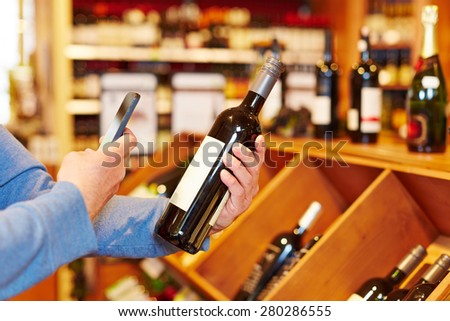 Hand with smartphone scanning wine bottle in supermarket for price comparison - stock photo