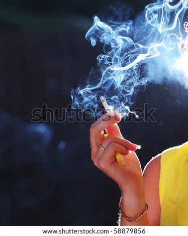 Hand with smoking cigarette. Close-up, shallow DOF. - stock photo