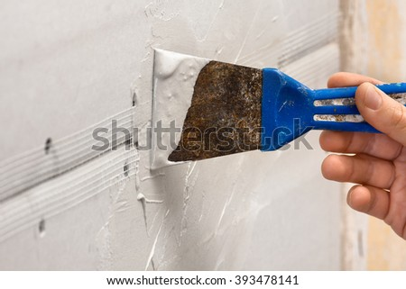 hand with spatula plastering a wall - stock photo