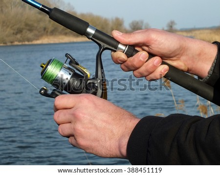 hand with spinning and reel on the riverbank