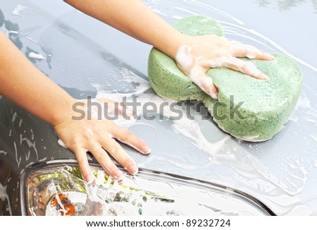 Hand with sponge cleaning car - stock photo