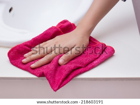Hand with sponge cleaning white sink.