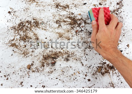 Hand with sponge wiping a dirty surface - stock photo