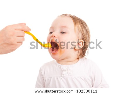hand with spoon feeding baby - stock photo