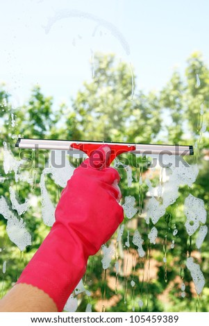 hand with squeegee on window pane - stock photo
