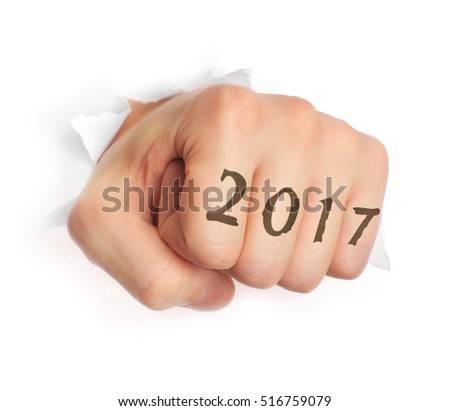 Hand with 2017 tattoo punching through paper isolated on white