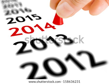 Hand with the game piece taking the next step from the year number 2013 to the next year 2014 - stock photo