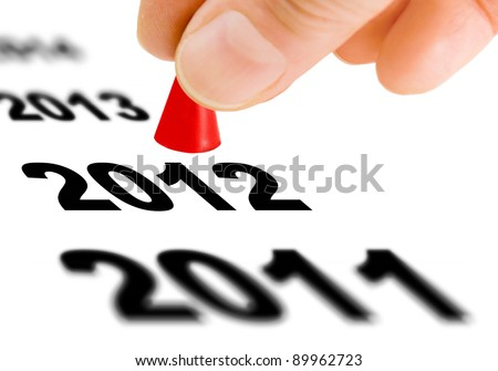Hand with the game piece taking the next step from the year number 2011 to the next year 2012 - stock photo