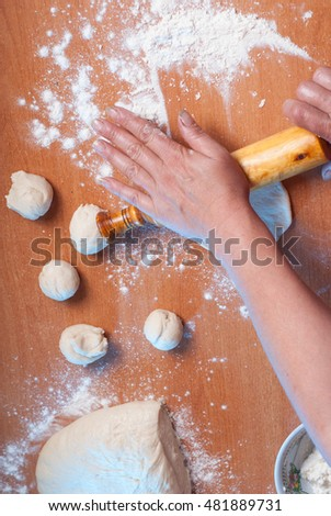 hand with thumb roller and dough on a wooden table, the cook preparing the dough