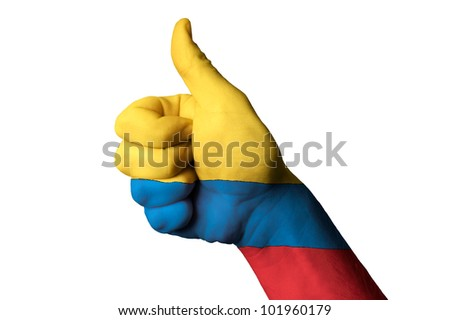 Hand with thumb up gesture in colored colombia national flag as symbol of excellence, achievement, good, - for tourism and touristic advertising, positive political, social management of country - stock photo
