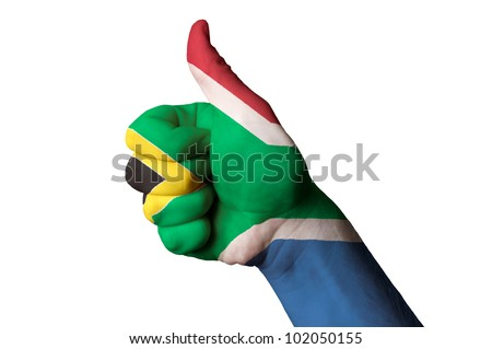 Hand with thumb up gesture in colored south africa national flag as symbol of excellence, achievement, good, - for tourism and touristic advertising, positive political, social management of country - stock photo