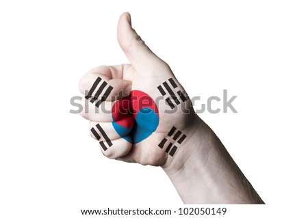 Hand with thumb up gesture in colored south korea national flag as symbol of excellence, achievement, good, - for tourism and touristic advertising, positive political, social management of country - stock photo