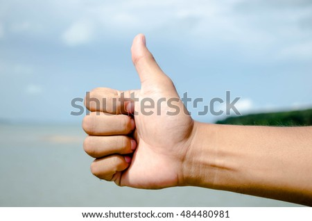 Hand with thumb up isolated on sky background. Ok sign by man