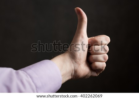 Hand with thumb up on dark background. - stock photo