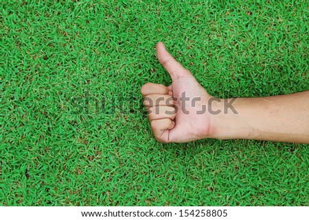 Hand with thumb up on green grass background texture