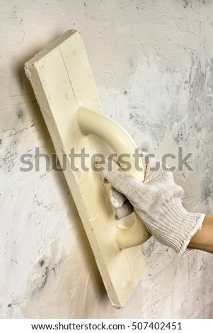 hand with trowel plastering concrete wall during repair