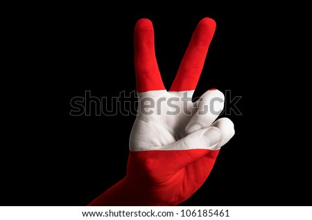 Hand with two finger up gesture in colored austria national flag as symbol of winning, - for tourism and touristic advertising, positive political, cultural, social management of country