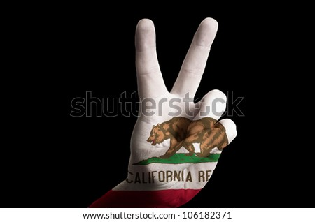 Hand with two finger up gesture in colored california state flag as symbol of winning,  - for tourism and touristic advertising, positive political, cultural, social management of country - stock photo