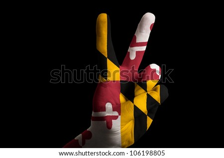Hand with two finger up gesture in colored maryland state flag as symbol of winning,  - for tourism and touristic advertising, positive political, cultural, social management of country - stock photo