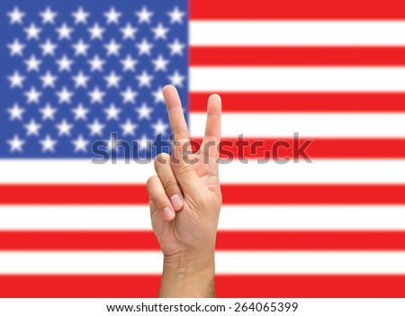 hand with two fingers in victory concept with flag of USA background