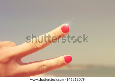 Hand with two fingers up in the peace or victory symbol and nature background - stock photo