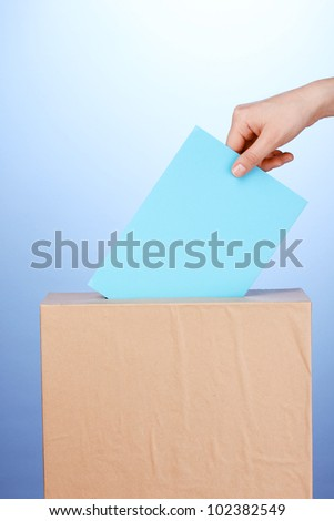 Hand with voting ballot and box on blue background - stock photo