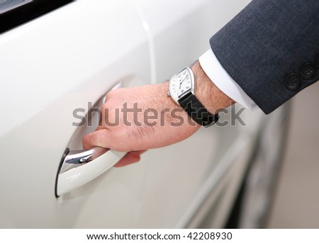 hand with watch opening luxury car door - stock photo