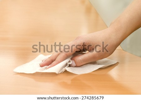 hand with wet wipe cleaning table - stock photo