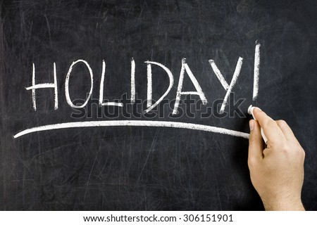 Hand with white chalk underlining handwritten holiday text on dirty blackboard
