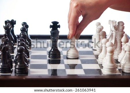 Hand with white pawn moves to black king closeup - stock photo